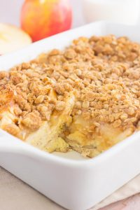 french toast casserole in a white dish with a piece cut out