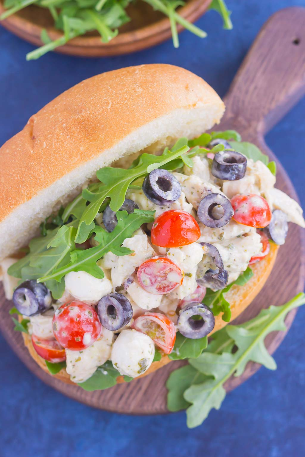 This Italian Chicken Salad is fresh, easy, and bursting with flavor. Loaded with mozzarella cheese, tomatoes, black olives and pesto, this fun twist on a classic flavor will have you coming back for more. This salad is perfect for an easy lunch or dinner and makes delicious sandwiches, too!
