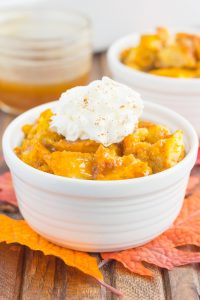 pumpkin bread pudding in a white bowl with a dollop of whipped cream