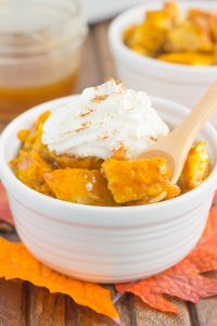 pumpkin bread pudding in a white bowl with a spoon