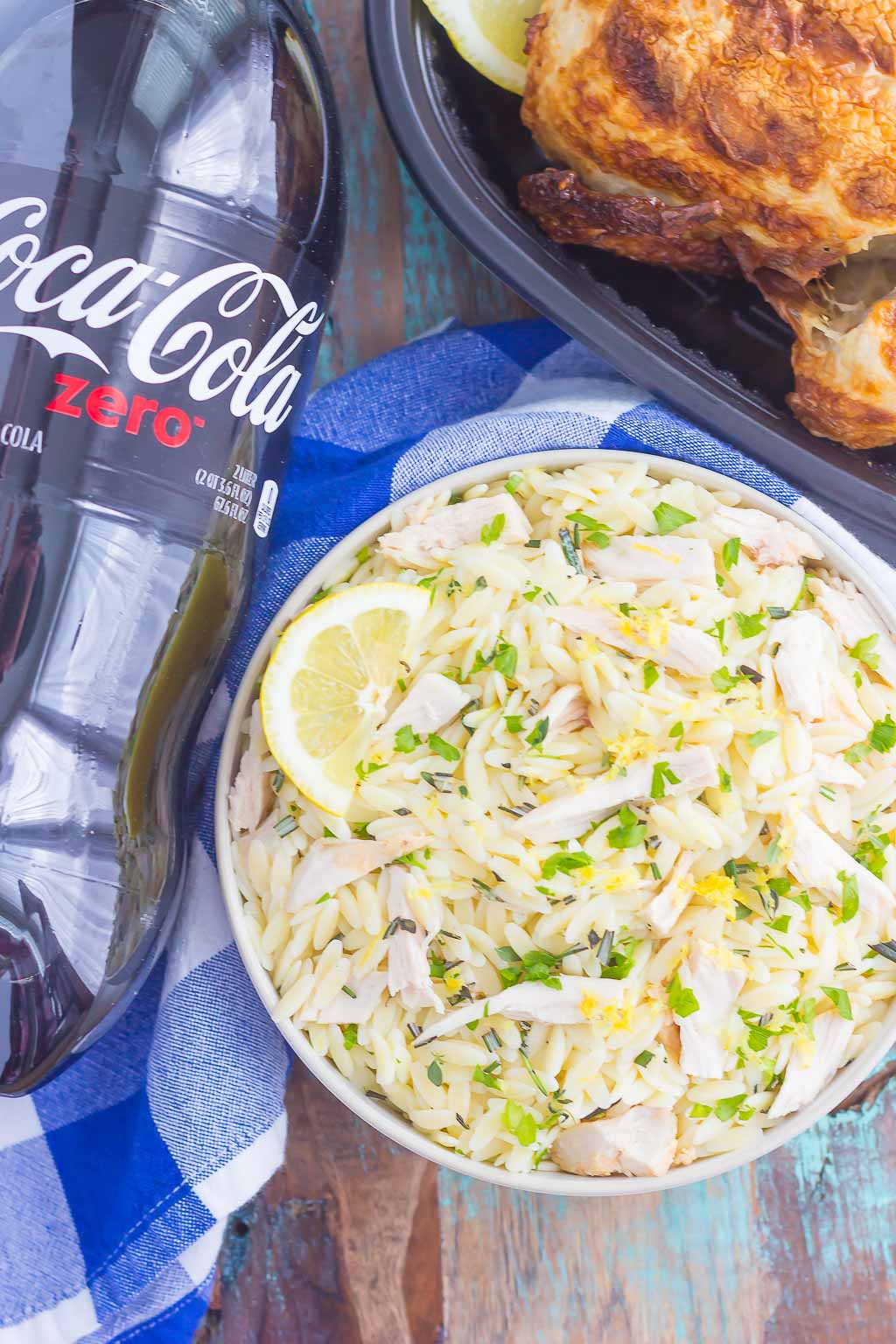 overhead shot of bowl of lemon orzo pasta salad next to bottle of coca cola and rotisserie chicken