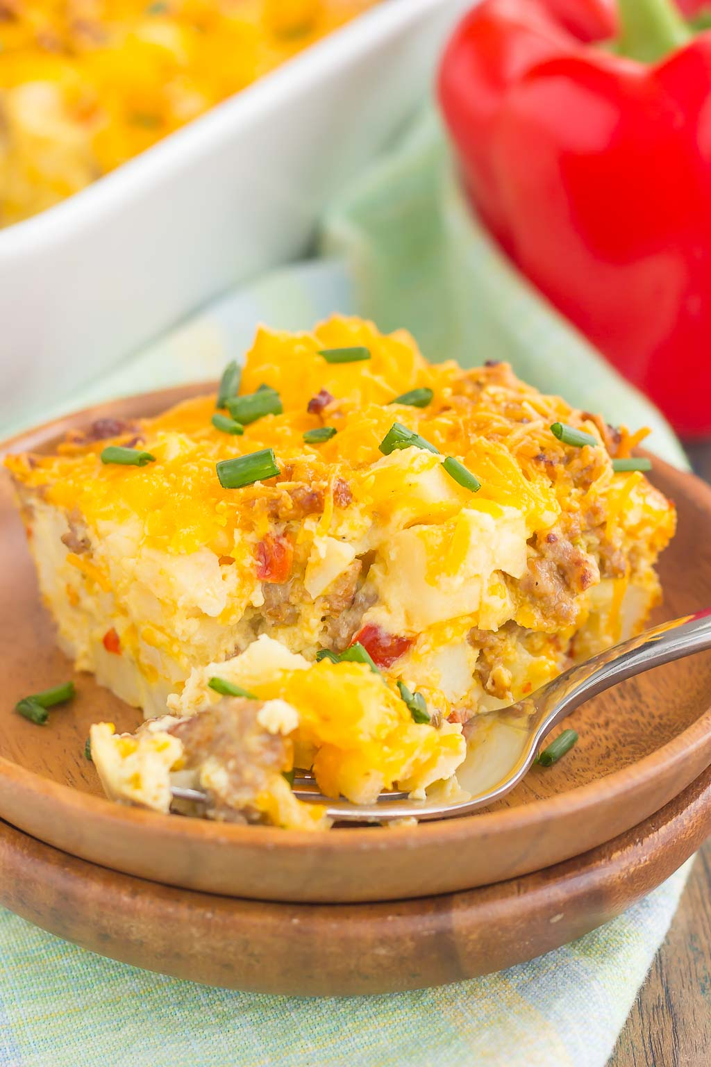 a slice of sausage hashbrown breakfast casserole on a wooden plate with a fork.
