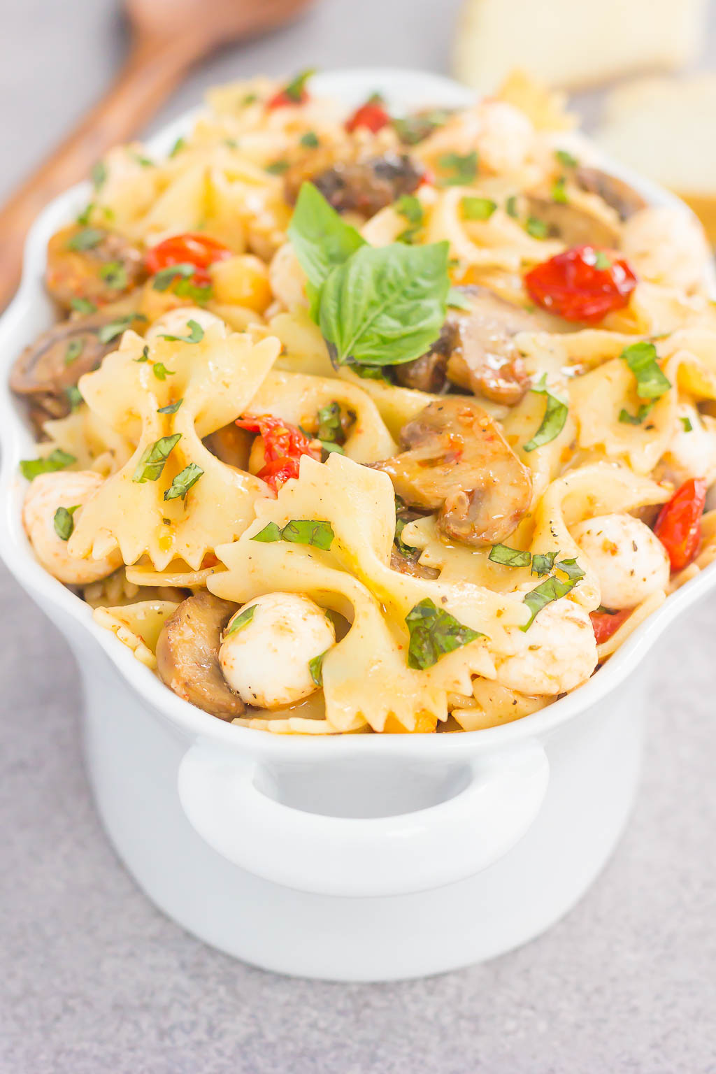 This Roasted Mushroom and Tomato Pasta Salad is a flavorful dish that comes together in minutes. Fresh mushrooms and cherry tomatoes are roasted until tender and then tossed with chickpeas, mozzarella and pasta in a light, white balsamic dressing. Bursting with flavor and perfect for a light lunch or dinner, you'll be making this pasta salad all year long!