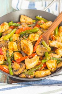 pan of easy chicken stir-fry with a wooden spoon
