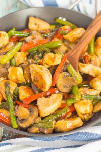 honey garlic chicken stir-fry in a pan with a wooden spoon