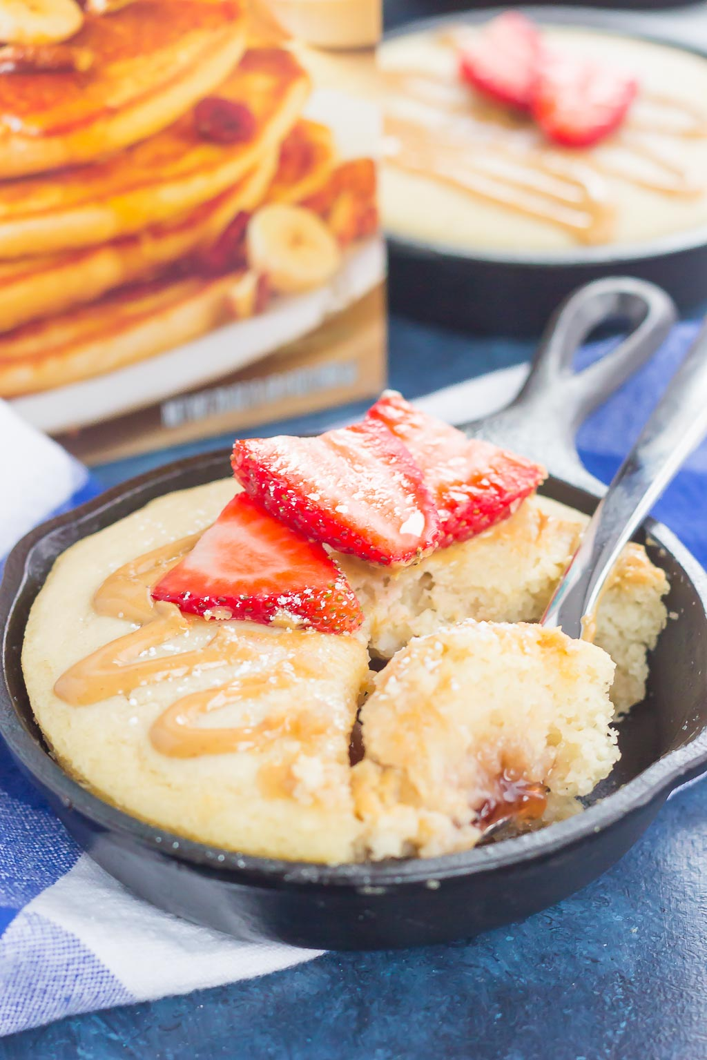 Peanut Butter and Jelly Baked Pancakes are a warm and cozy breakfast to get you going in the mornings. Fluffy, buttermilk pancake batter is swirled with sweet strawberry jelly and then baked in mini cast iron skillets. Drizzled with a sweet peanut butter syrup and topped with fresh strawberries, this easy breakfast is ready in less than 30 minutes and perfect for the whole family!
