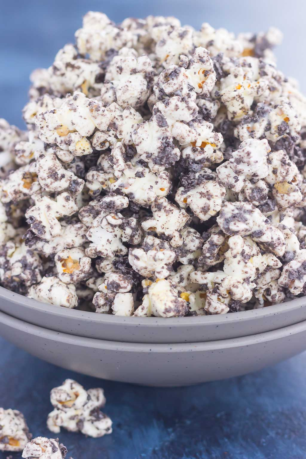Side view of an overflowing bowl of cookies and cream popcorn.