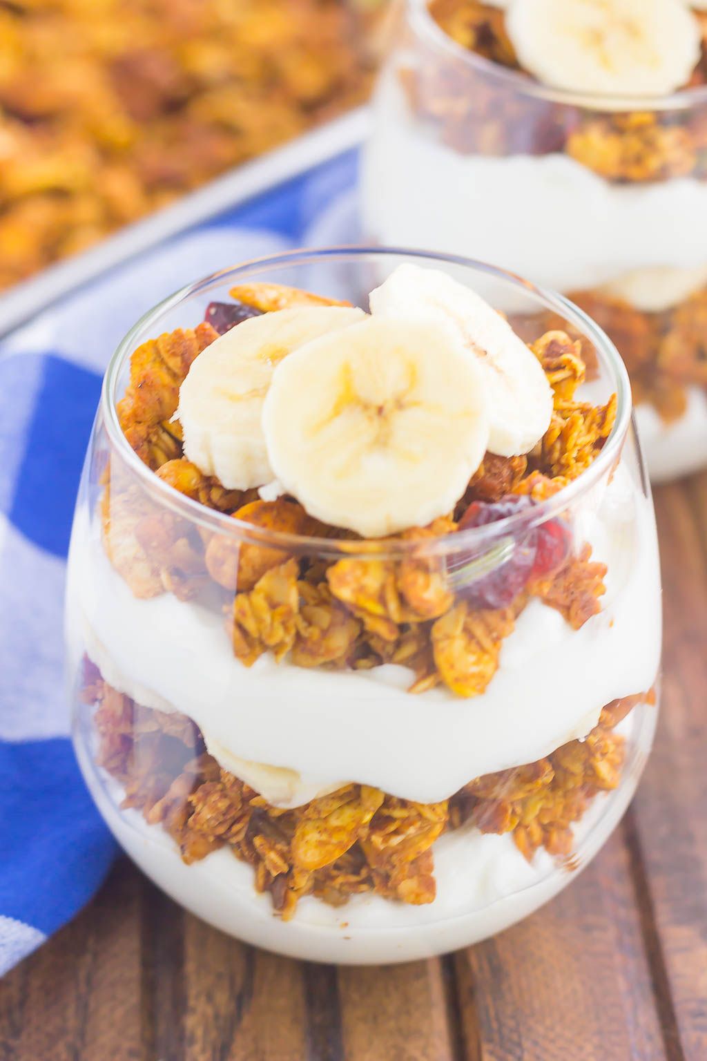 yogurt and pumpkin granola and banana slices layered in a glass