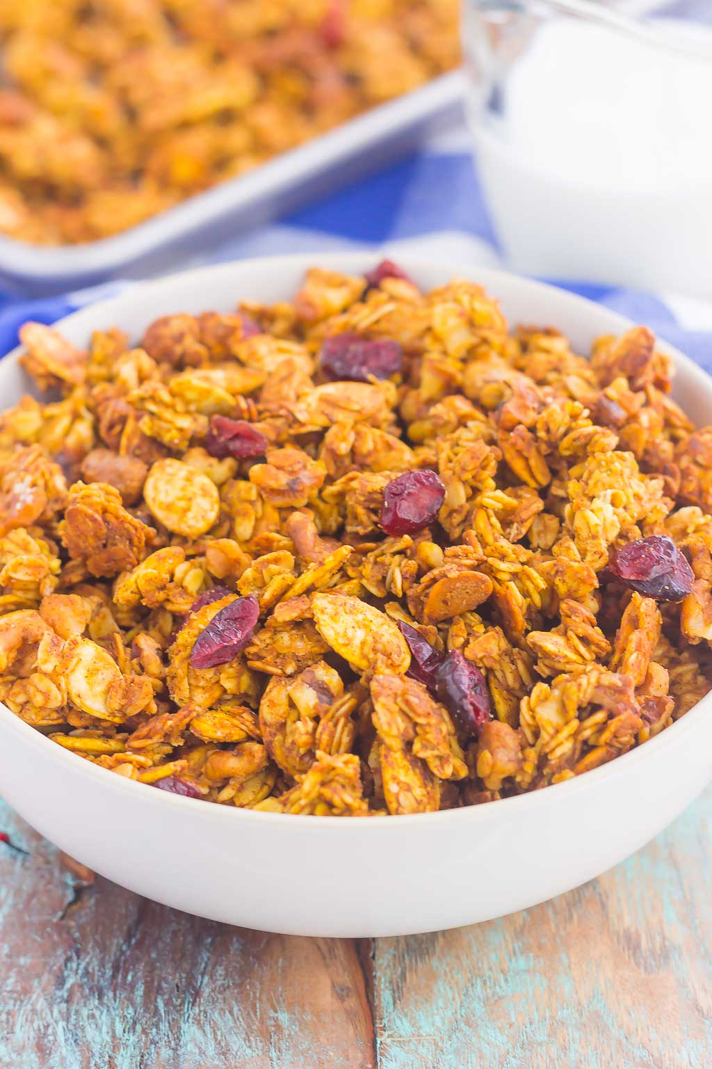 This Pumpkin Spice Granola is a delicious way to savor the flavors of fall. Hearty oats, crunchy walnuts, dried cranberries and fall spices give this granola both texture and flavor. It's simple to make and perfect to eat by the handful, with milk, or on top of yogurt or ice cream! #granola #pumpkingranola #homemadegranola #pumpkinbreakfast #pumpkinsnack #healthygranola