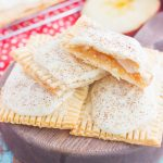 These Apple Pie Pop Tarts are an easy treat that's perfect for breakfast or dessert. Flaky pie crust surrounds sweet apple pie filling and is frosted with white chocolate and apple pie spice. Simple to make and better than the store-bought kind, you'll love the cozy taste of these homemade pop tarts!