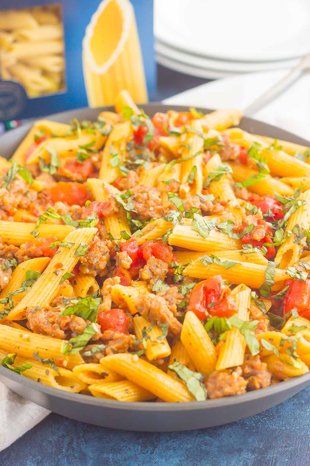 tomato basil pasta with italian sausage in large gray bowl