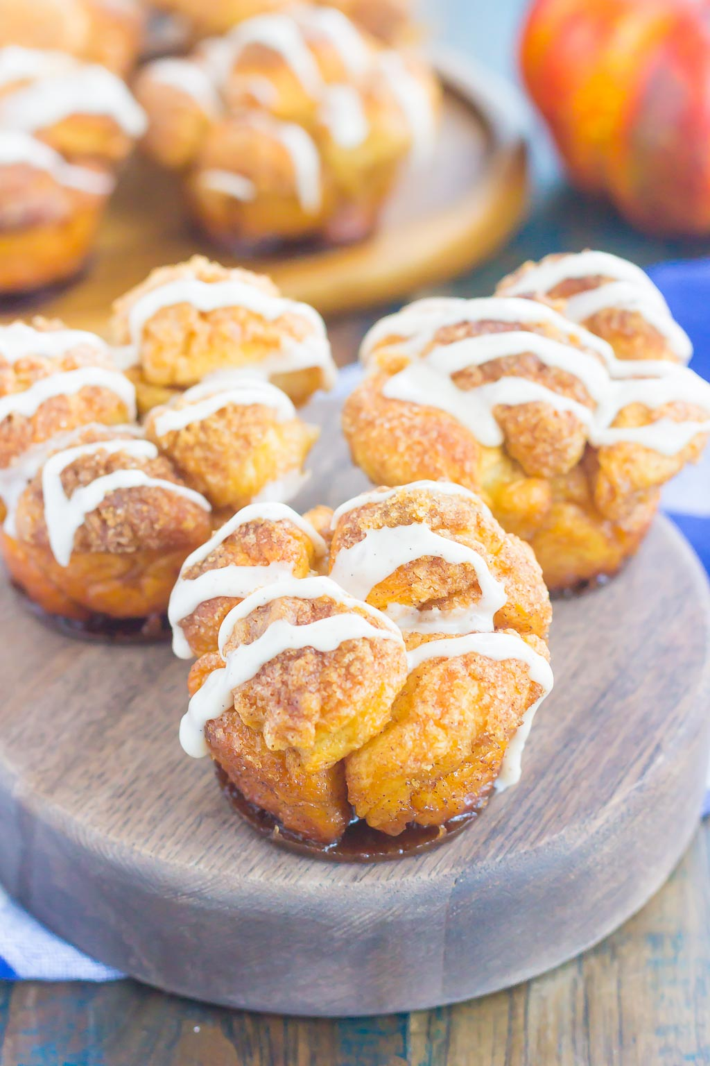 These Pumpkin Spice Monkey Bread Muffins are a simple treat that's perfect for breakfast or dessert. Pre-made dough is rolled in a cozy pumpkin spice blend and then baked in muffin cups. Topped with a sweet pumpkin glaze and great for the holidays, this gooey muffin is sure to impress everyone!