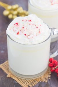 White chocolate hot chocolate in a mug garnished with whipped cream and peppermint candy