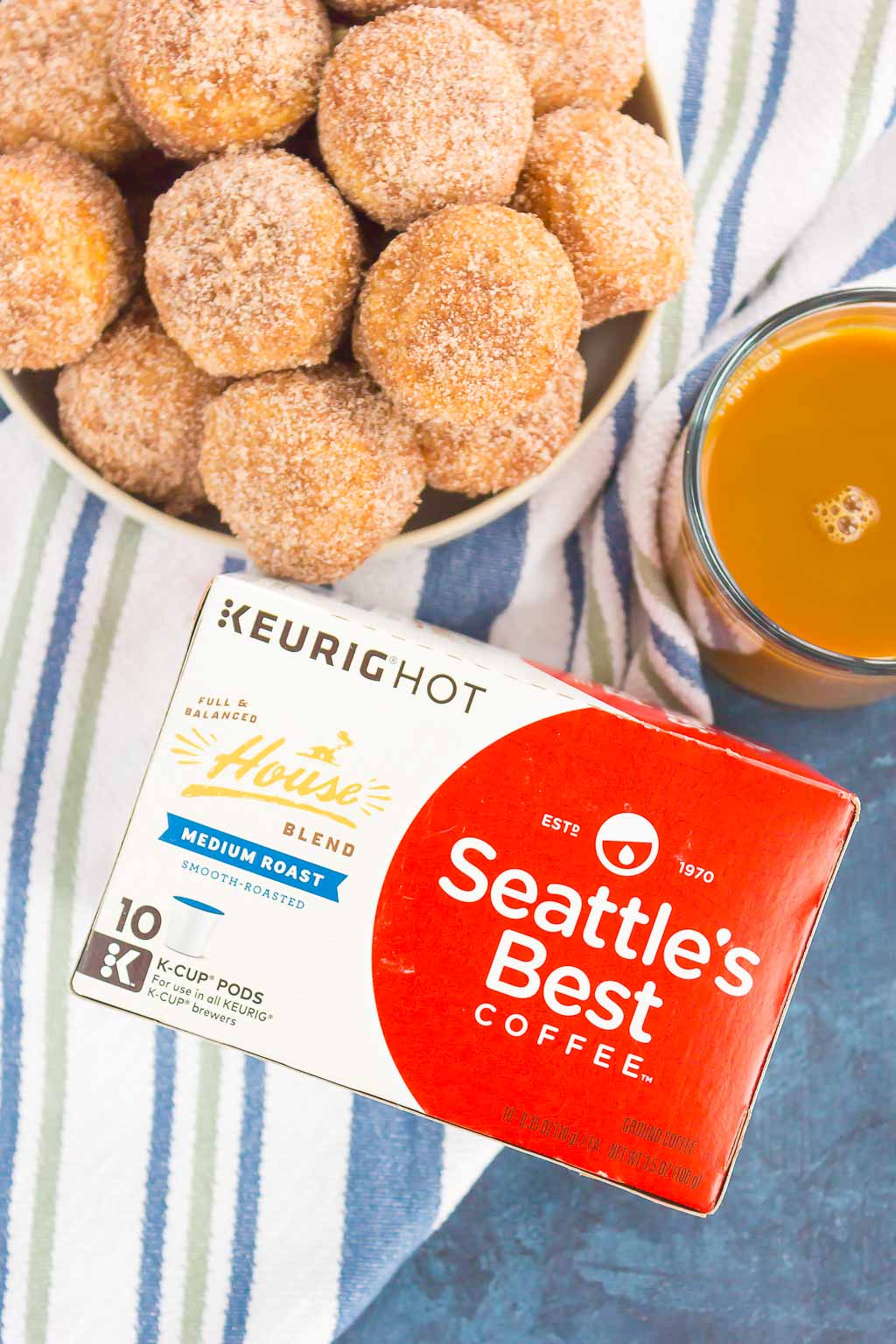 overhead view of cinnamon sugar baked donut holes piled in a white bowl next to a box of Seattle's Best k-cup pods