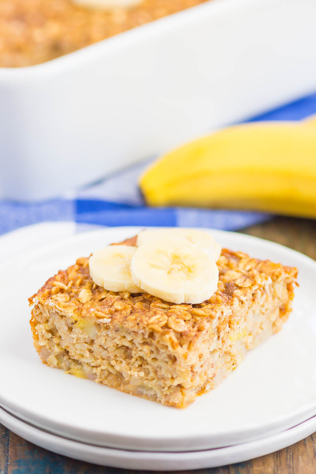 slice of banana baked oatmeal garnished with banana slices on white plate