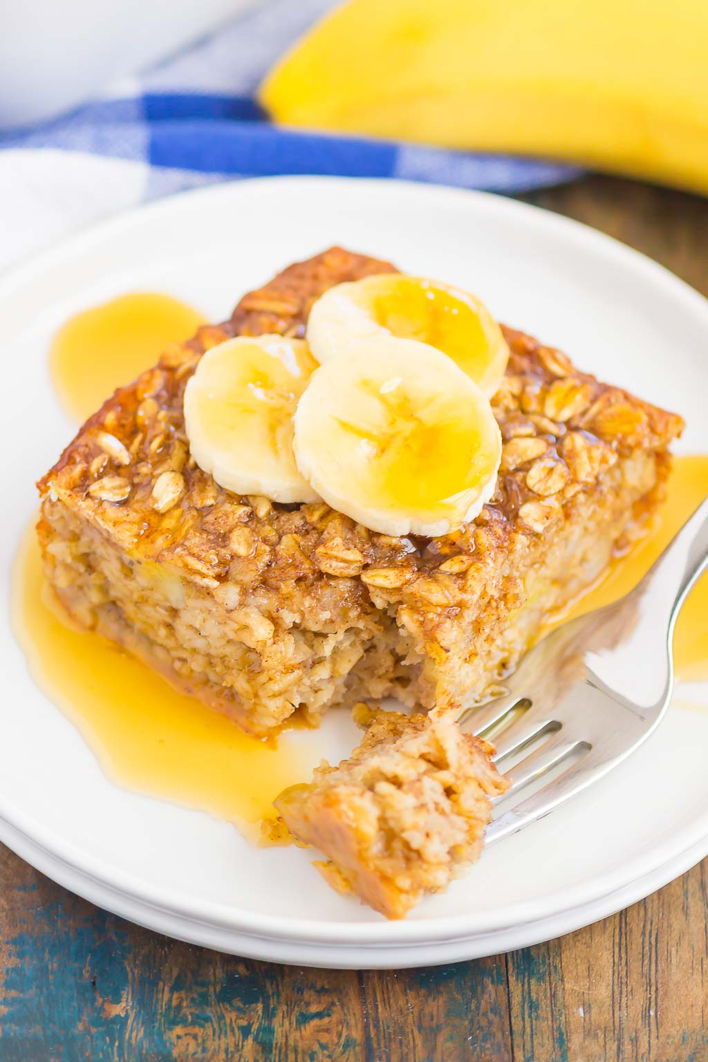 slice of banana baked oatmeal drizzled with honey on white plate with fork