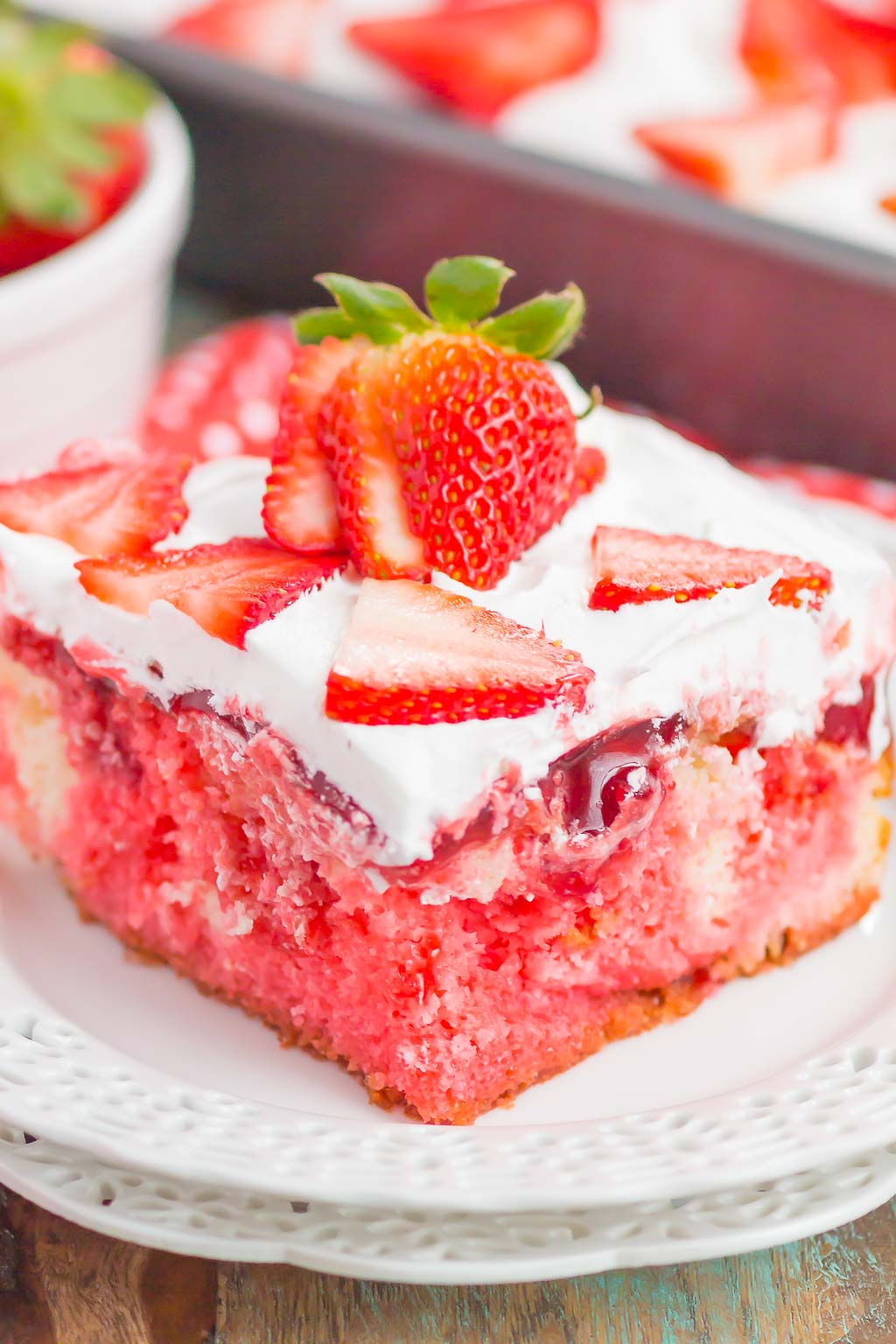 This Easy Strawberry Poke Cake features a vanilla cake that's studded with lots of strawberry flavor. Soft cake is drizzled with sweet strawberry jello and then topped with a strawberry glaze and a creamy whipped topping. Simple to make and even better to eat, you'll love this moist and fresh cake!
