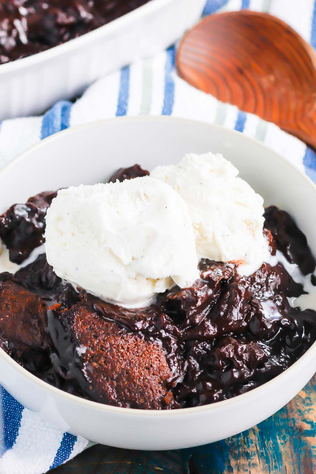 serving of chocolate cobbler topped with ice cream in a white bowl. a wooden spoon rests in the background.