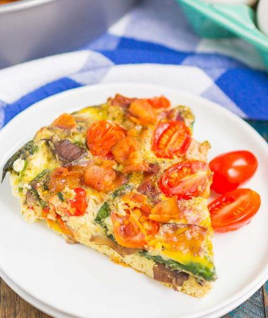This Bacon and Tomato Frittata is a simple dish that's ready in less than an hour. Filled with crisp bacon, tender mushrooms, spinach and tomatoes, this recipe makes a delicious breakfast or brunch! #frittata #frittatarecipe #easyfrittata #bacon #baconfrittata #tomatofrittata #mushroomfrittata #breakfast #easybreakfast #breakfastrecipe