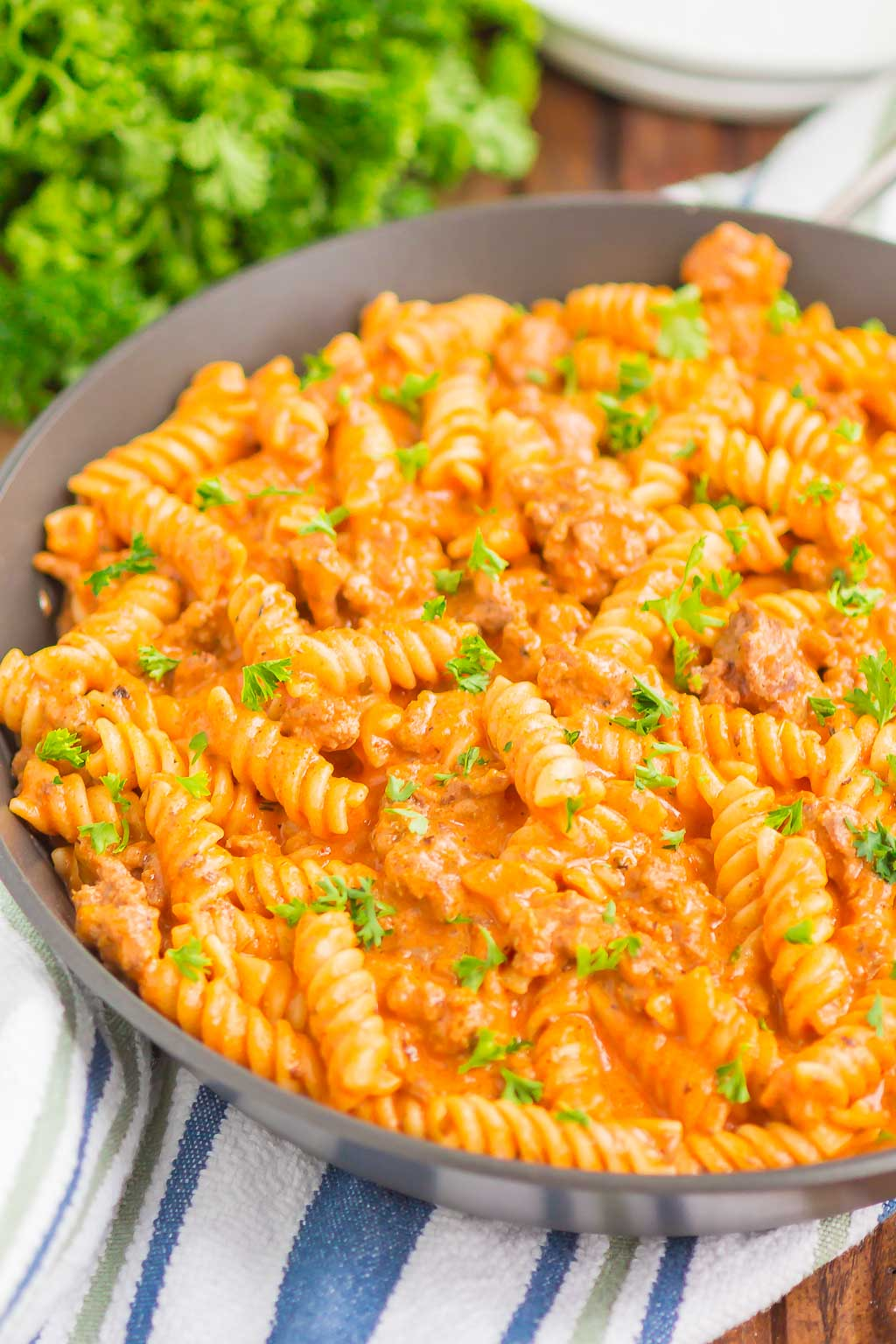 ground beef pasta in a skillet next to bunch of parsley