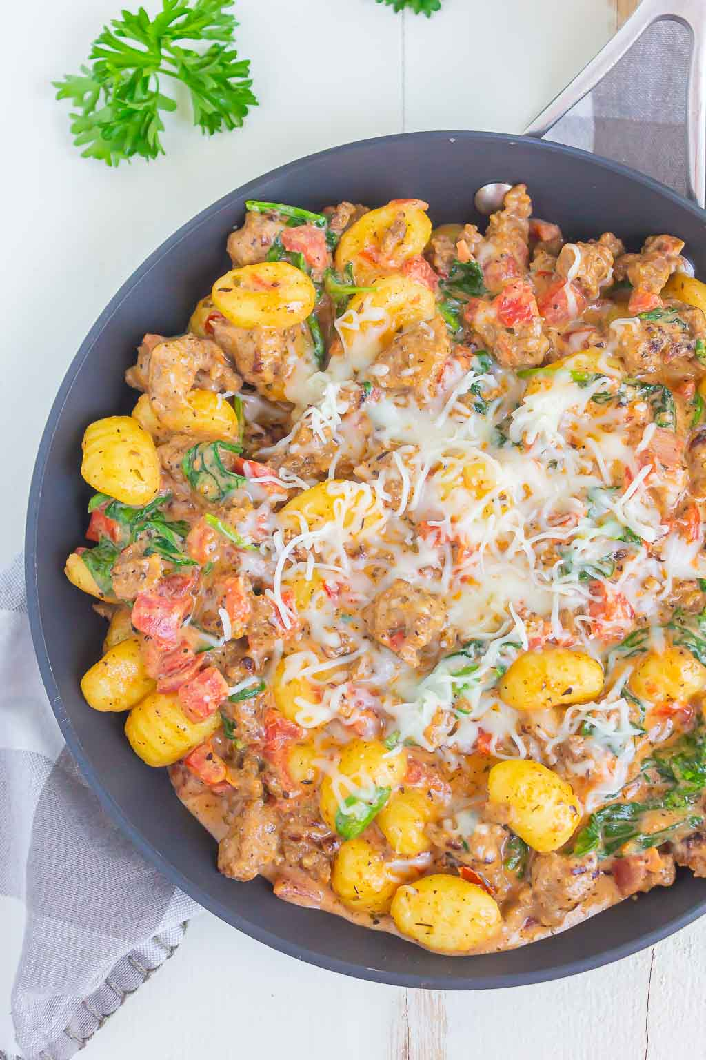 Overhead view of a skillet of Italian sausage gnocchi, topped with shredded mozzarella cheese.