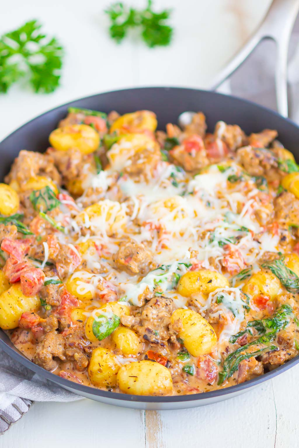 A skillet of Italian sausage gnocchi, topped with shredded mozzarella cheese.